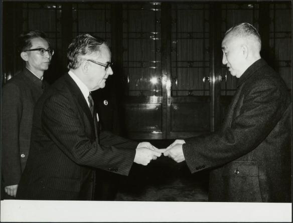 Photographie en noir et blanc de deux hommes qui se saluent. L'un des deux hommes tient un bout de papier et le tend à l'autre. Un homme se trouvant à l'arrière-plan regarde la scène.