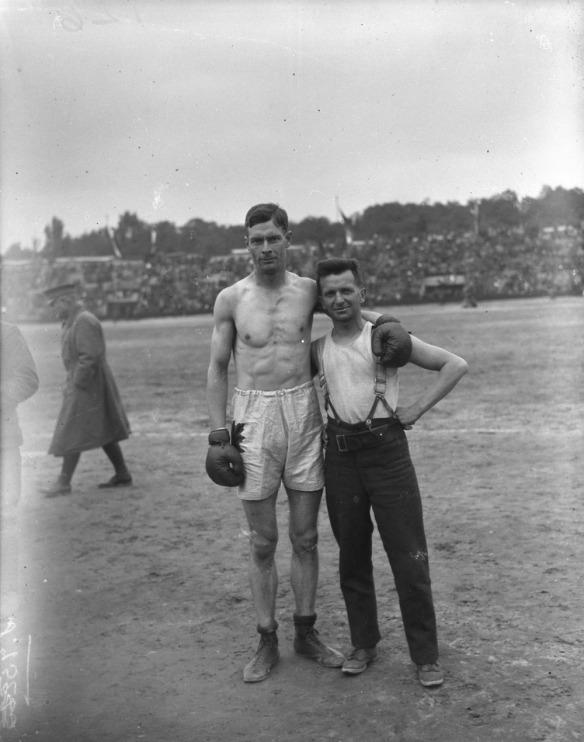 Photographie en noir et blanc du boxeur de la catégorie des poids moyens Edwin A. Harris (Canada), portant le short et les gants. Un autre soldat se tient debout à ses côtés.
