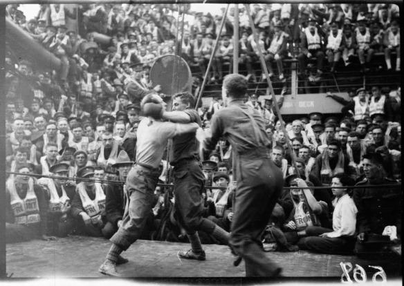 Photographie en noir et blanc de deux boxeurs s'affrontant sur le pont du navire à vapeur Justicia, sous le regard attentif des autres soldats se trouvant à bord.