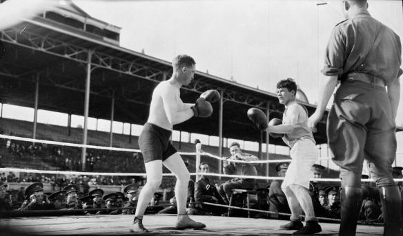 Photographie en noir et blanc de deux soldats qui s'affrontent à la boxe. L'un porte un short noir, et l'autre, un short blanc. Des soldats assis autour du ring assistent au combat.