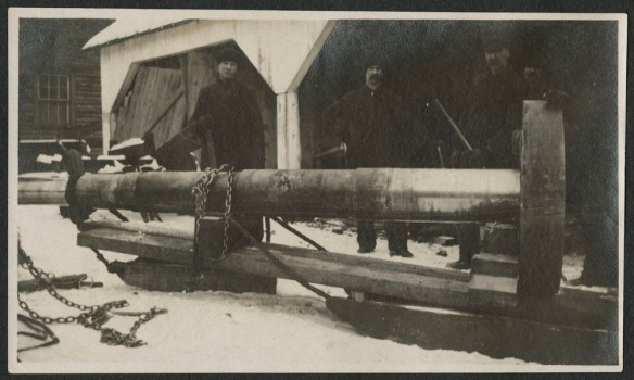 Photographie noir et blanc de quatre hommes debout derrière une large pièce tubulaire non décrite faisant partie du matériel de la scierie.