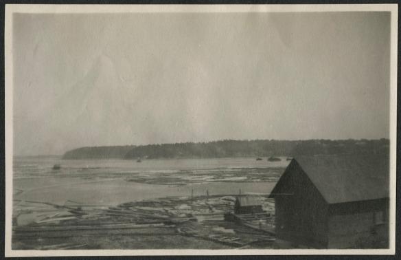 Photographie noir et blanc de la scierie Gilmour and Hughson sur le bord de la rivière. La scierie est au premier plan. Des billes de bois flottent sur la rivière et le long de la berge.