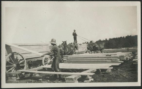 Photographie noir et blanc d'un homme chargeant du bois de charpente sur un chariot tiré par des chevaux. Un deuxième chariot mené par un conducteur et rempli de madriers s'apprête à quitter les lieux.