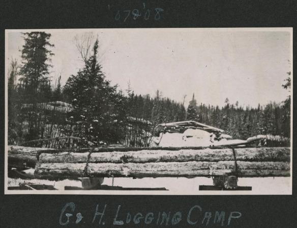 Photographie noir et blanc d'un chantier de la Gilmour and Hughson pendant l'hiver. On y voit à l'arrière-plan des cabanes en bois rond le long d'une rangée d'arbres. À l'avant-plan, des rondins fraîchement coupés sont empilés et retenus par des chaînes.