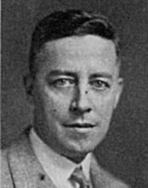 Photographie en noir et blanc d'un homme vêtu d'un veston gris qui fixe l'objectif.