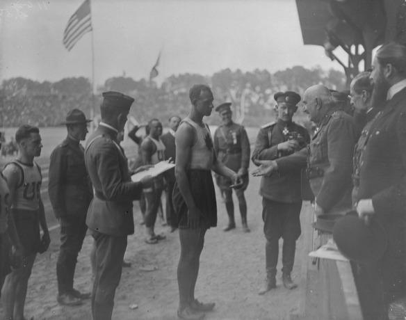 Une photographie noir et blanc d'un homme portant une tenue d'athlétisme, entouré d'autres hommes vêtus de la même manière ou en uniformes, recevant une médaille d'un homme âgé vêtu d'un uniforme militaire.