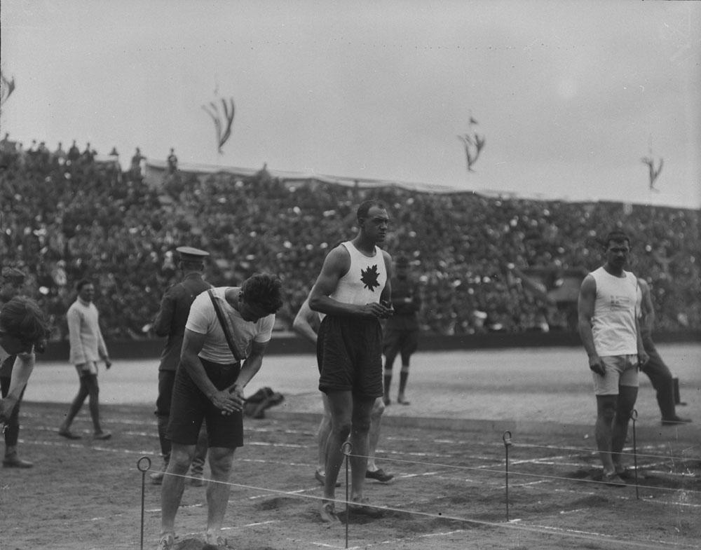 Une photographie noir et blanc d'un groupe de coureurs à la ligne de départ. Un d'entre eux porte un maillot blanc orné d'une feuille d'érable sur le devant.