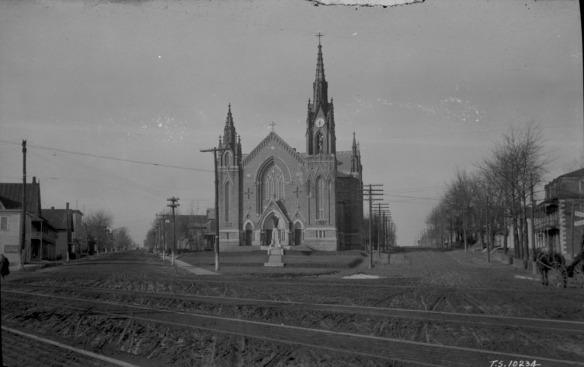 Photo noir et blanc d'une grande église dans un petit village. On peut voir des voies de chemin de fer dans l'avant plan.