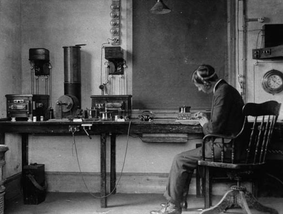 Photographie en noir et blanc de Donald Manson, un employé de la compagnie Marconi assis à une table et coiffé d'écouteurs, qui écrit sur du papier tout en écoutant une transmission radio.