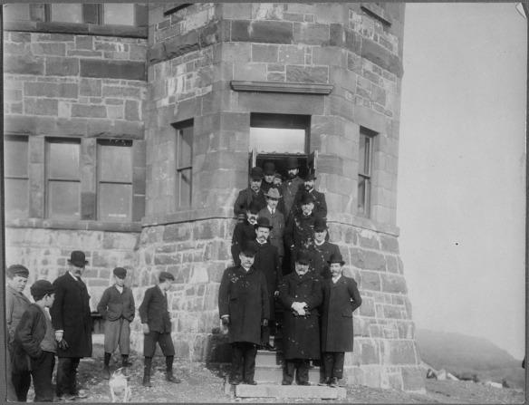 Photographie en noir et blanc de Guglielmo Marconi posant sur les marches d'un bâtiment avec 12 membres de l'administration de Terre-Neuve, colline Signal, St. John's.