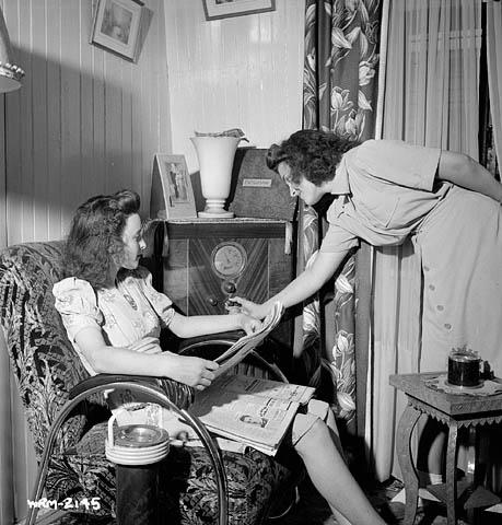 Photographie en noir et blanc de deux femmes écoutant la radio, l'une assise dans un fauteuil et l'autre, debout, ajustant les réglages du poste.