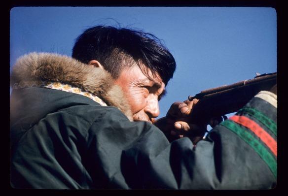 Photographie couleur d'un homme de profil tenant un fusil et ajustant son tir. Il porte un parka traditionnel au capuchon bordé de fourrure et aux manches ornées de galons verts et rouges.