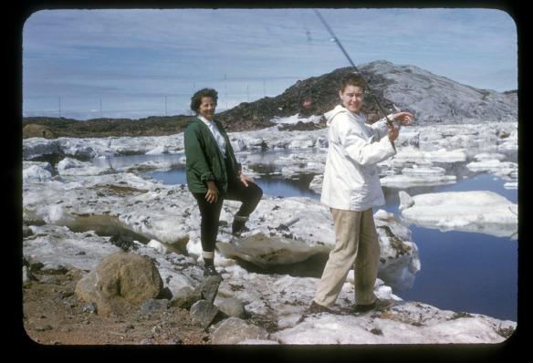 Photographie couleur de deux femmes en train de pêcher sur les rives d'un plan d'eau. Elles sont debout sur des roches, et des plaques de glace flottent sur l'eau.