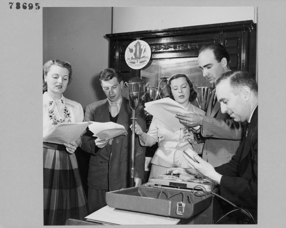 Photographie en noir et blanc de deux femmes et de trois hommes, membres de la troupe de radiothéâtre RA, lisant dans un microphone à partir d'un texte.