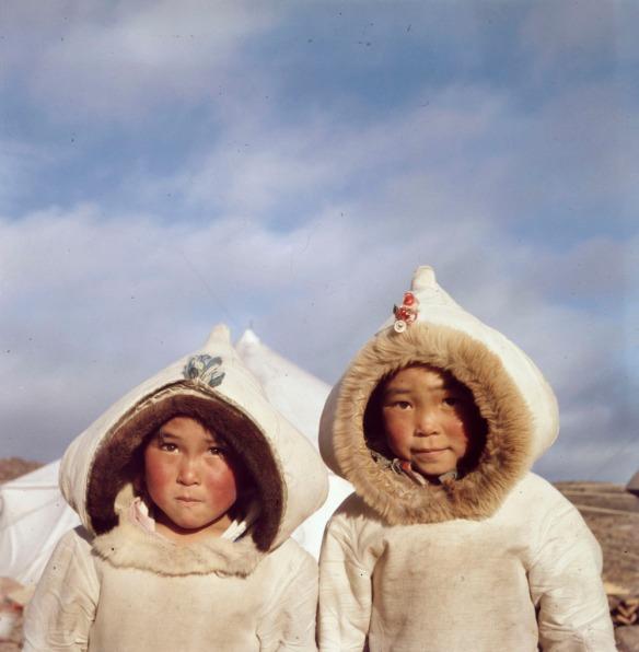 Photographie couleur de deux enfants inuits portant un manteau traditionnel devant une tente blanche dans un paysage rocailleux.