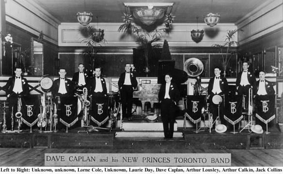 Photo noir et blanc d'un orchestre de danse, avec musiciens en tenue de soirée debout sur un podium devant leurs instruments de musique