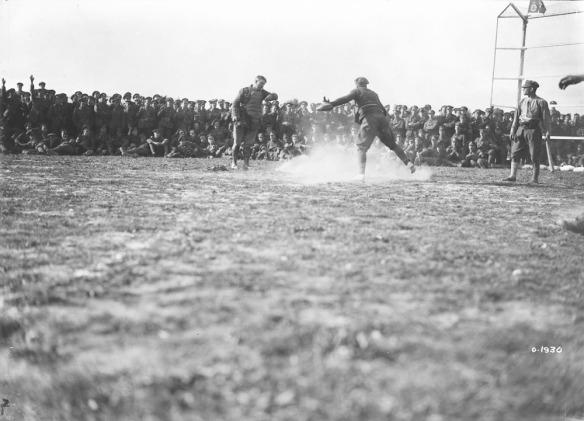 Une photographie noir et blanc d'un joueur glissant vers le marbre. Le receveur se tient derrière le marbre alors que l'arbitre rend sa décision. Une foule composée de soldats les encourage.