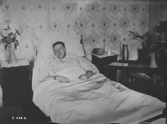 Une photographie en noir et blanc d'un jeune homme souriant dans un lit.
