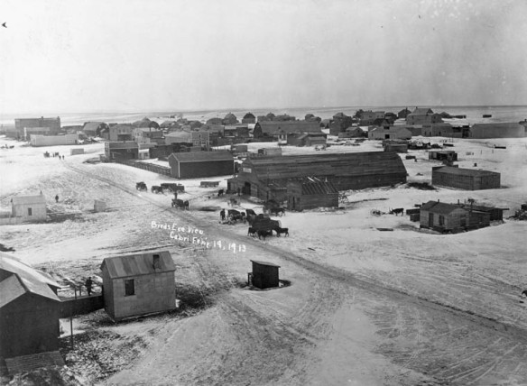 Une photographie en noir et blanc de Cabri (Saskatchewan), à partir d'une vue à vol d'oiseau. On aperçoit un chemin de terre principal ainsi que des résidences et des bâtiments voisins. Quelques personnes, chevaux et chariots se rassemblent dans le village.