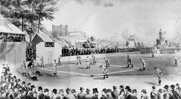 Une photographie noir et blanc d'un terrain de baseball extérieur où une partie est en cours. Une foule compacte y assiste dans les gradins. Des édifices de la ville se dessinent à l'arrière-plan.