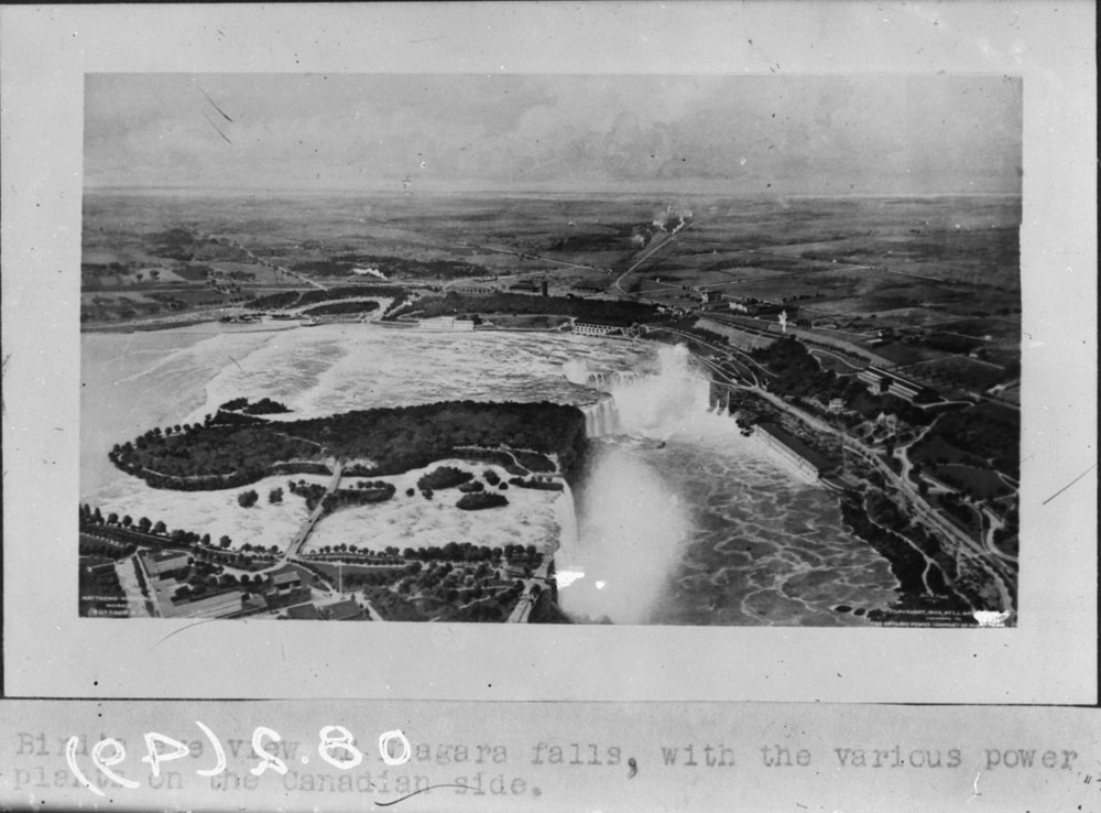 Une photographie en noir et blanc des chutes Niagara, à partir d'une vue à vol d'oiseau. On aperçoit divers bâtiments des deux côtés de la frontière ainsi que des routes menant aux rives.