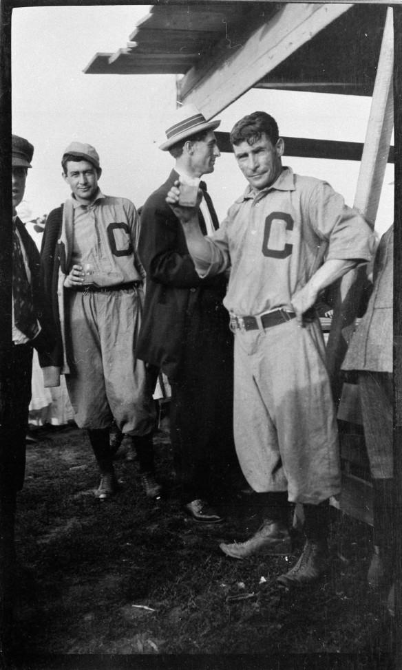 Photo noir et blanc de cinq hommes debout devant un comptoir. Deux d'entre eux sont vêtus d'un uniforme de baseball orné d'un grand « C » sur la poitrine; les autres portent un complet et un chapeau. Un des hommes en uniforme tient une boisson dans sa main et regarde l'objectif.