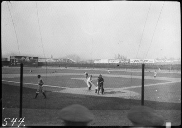 Une photographie noir et blanc d'une partie de baseball prise de l'arrière du marbre. Un joueur est au marbre, prêt à recevoir un lancer. L'arbitre est debout derrière le receveur pour rendre sa décision.
