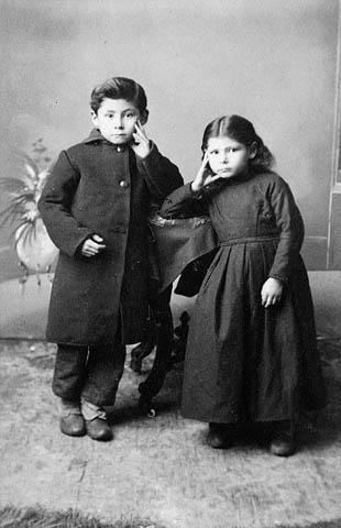 Photo noir et blanc de deux enfants appuyés contre un guéridon, une main sur la joue.