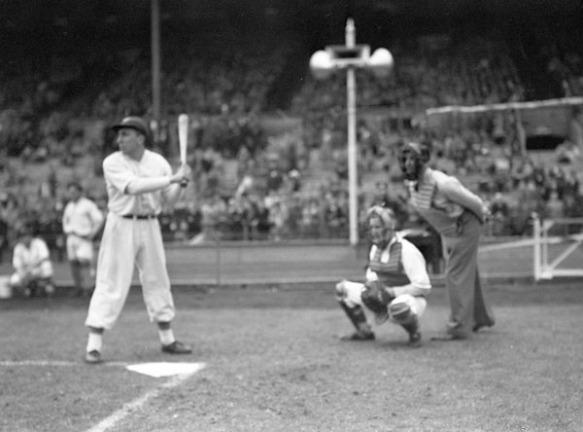 Une photographie noir et blanc d'une partie de baseball. Le frappeur est debout levant un bâton et, derrière lui, le receveur et un arbitre. À l'arrière-plan, on aperçoit des joueurs guettant le jeu et des spectateurs dans les gradins.