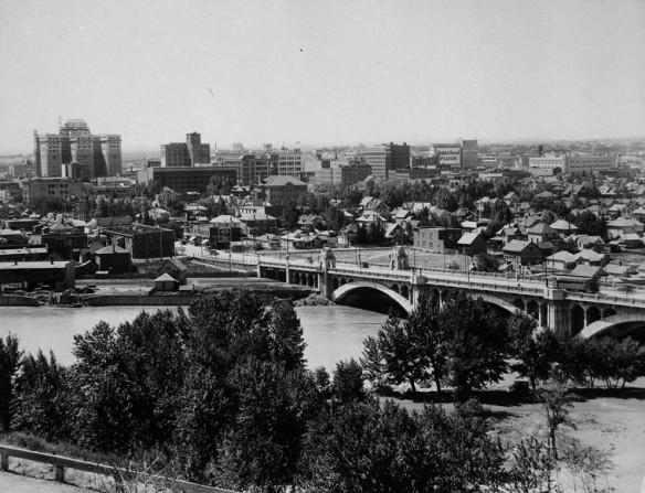 Une photographie en noir et blanc de Calgary (Alberta), à partir d'une vue à vol d'oiseau. On aperçoit au premier plan la rivière Bow et un pont ainsi qu'un certain nombre de résidences et de gros bâtiments en arrière-plan.