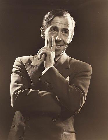 Photographie en noir et blanc montrant un homme en complet avec les bras croisés et une main cachant une partie de son visage. Son regard est à la droite du photographe.