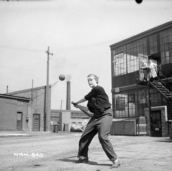 Une photographie noir et blanc d'une femme portant des vêtements de travail et un foulard noué sur la tête s'apprête à frapper une balle avec son bâton. Elle est debout dans la cour arrière d'un bâtiment industriel, et l'on voit d'autres structures à l'arrière-plan.