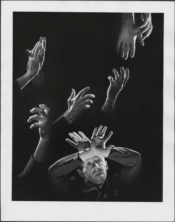 Une photographie composite en noir et blanc montrant les mains expressives de Gratien Gélinas dans différentes poses. Dans le bas de la photo, on voit un homme tenant ses mains croisées au-dessus de sa tête.