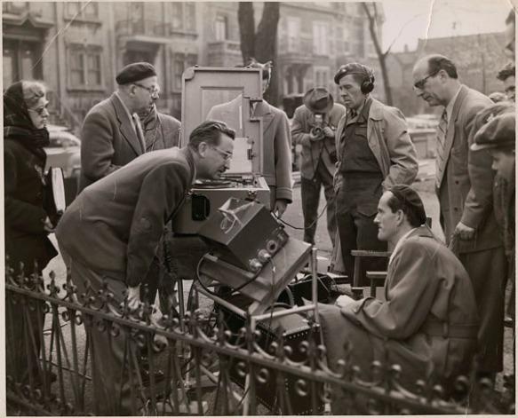 Photographie en noir et blanc d'une scène de tournage montrant plusieurs personnes regroupées autour d'une caméra.