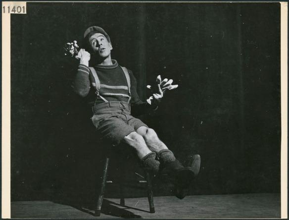 Photographie en noir et blanc montrant un homme habillé en pantalon court avec des bretelles et une casquette.