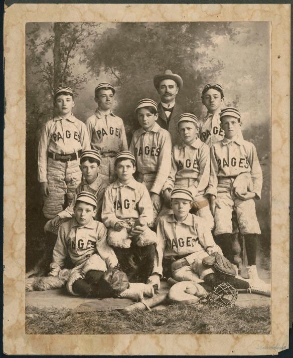 Une photographie noir et blanc de 10 enfants vêtus d'un uniforme de baseball. Les chandails portent l'inscription « Pages » sur le devant. Certains des garçons sont assis et d'autres debout avec des bâtons, des gants et d'autres équipements de baseball. Un homme adulte, portant un costume et un chapeau, se tient debout derrière les garçons. L'arrière-plan est une toile de fond montrant des arbres.