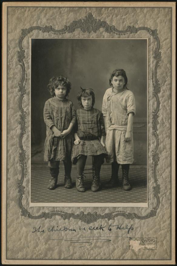 Photo noir et blanc de trois enfants : l'un assis au centre, et les deux autres debout.