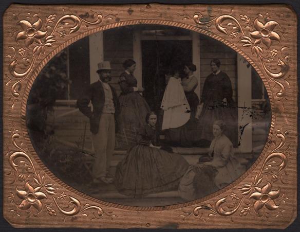 Photo noir et blanc encadrée de cinq femmes, d'un bébé, d'un homme et d'un chien, prenant la pose sur un balcon pour un portrait de famille.