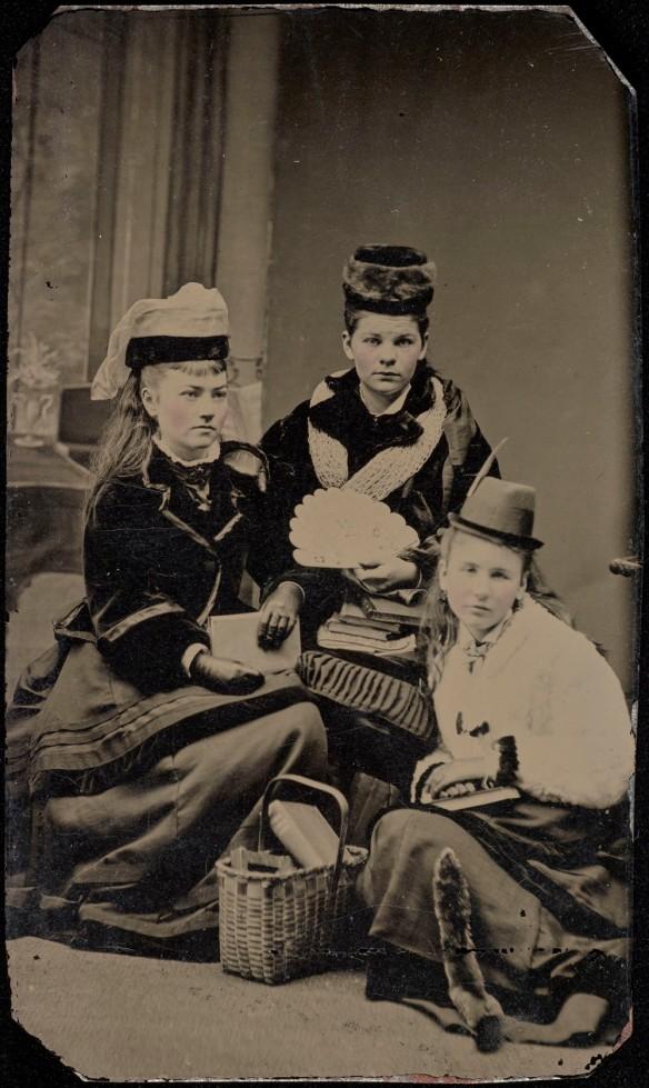 Photo noir et blanc de trois femmes prenant la pose pour un portrait. Elles sont vêtues de longues robes, de vestes et de chapeaux, et elles tiennent des livres.