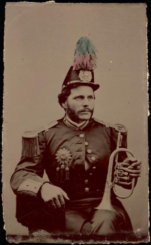 Photo noir et blanc d'un homme assis, vêtu d'un uniforme d'harmonie et d'un chapeau orné de plumes. L'homme tient un bugle (clairon) contre son genou gauche.