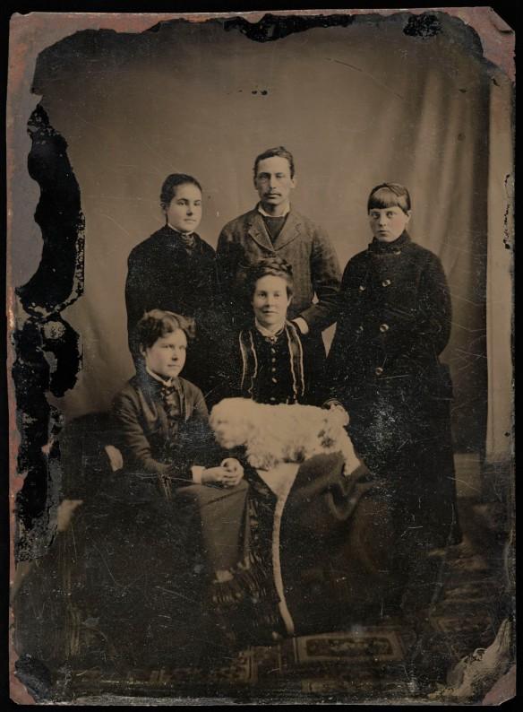 Photo noir et blanc d'une mère, de ses trois filles, de son fils et d'un chien, prenant la pose pour un portrait de famille.