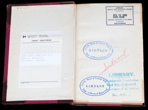 Photo couleur d'un livre ouvert aux pages de garde avant. On voit un ex-libris sur la page de gauche et quatre marques de tampon encreur sur la page de droite.
