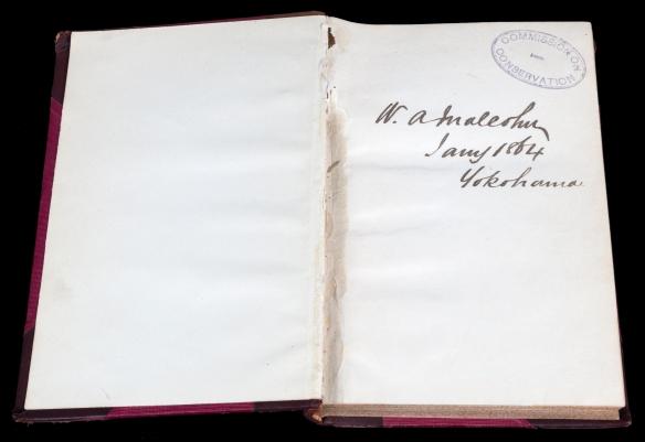 Photo couleur montrant deux pages d'un livre ouvert; sur la page de droite, on voit la marque d'un tampon encreur ainsi qu'une signature.