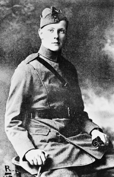 Une photographie en noir et blanc d'un officier assis, prenant la pose pour un portrait officiel. Il tient ses gants dans une main et un bâton dans l'autre.