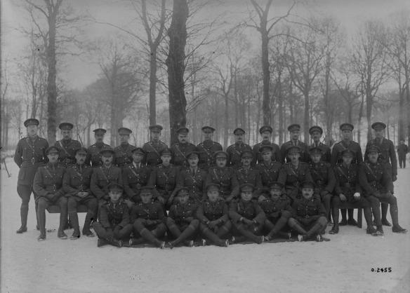 Photographie en noir et blanc d'un groupe de soldats debout et assis devant des arbres en hiver.