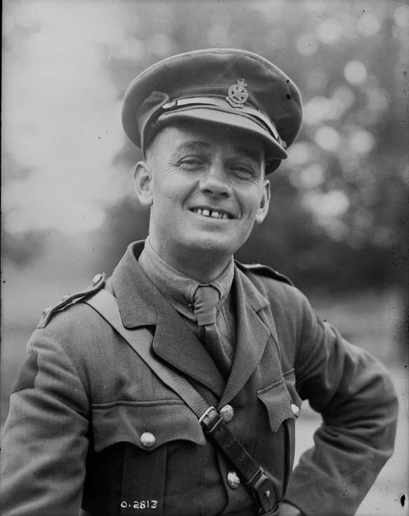 Photographie en noir et blanc d'un officier souriant.