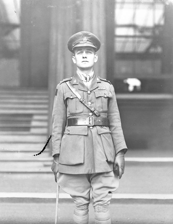 Photographie en noir et blanc d'un soldat, en uniforme d'officier avec des gants et une canne, debout devant des escaliers et une fenêtre.