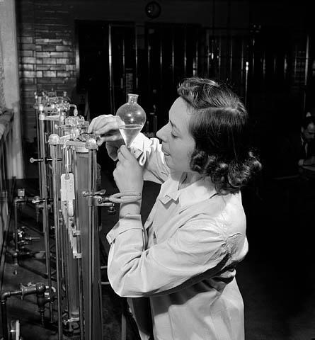 Photo noir et blanc d'une femme faisant des essais sur du caoutchouc synthétique au laboratoire de la Société Polymer.