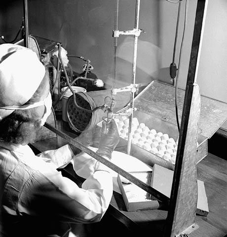 Photo noir et blanc d'une femme remplissant de pénicilline des fioles de 20 cm3 aux laboratoires Connaught.