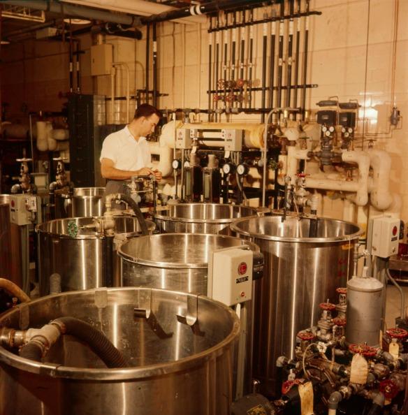 Photo en couleurs d'un homme préparant différents liquides utilisés pour le développement des films dans un laboratoire de mélange des produits chimiques de l'Office national du film du Canada.